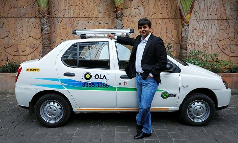 In this file photo, Bhavish Aggarwal, CEO and co-founder of Ola, an app-based cab service provider, poses in front of an Ola cab in Mumbai on March 3, 2015.— Reuters/File