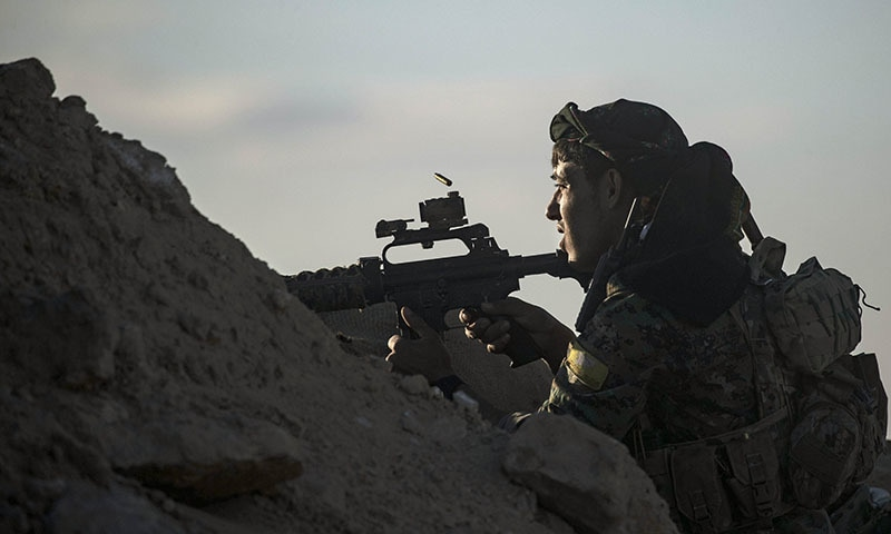 A fighter with the Syrian Democratic Forces keeps position at a hilltop as he watches the Islamic State (IS) group's last remaining location in the village of Baghouz on March 18, 2019 during battles with the Kurdish-led SDF in the countryside of the eastern Syrian province of Deir Ezzor. — AFP