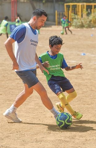MUMBAI: Former Spanish footballer Xavi Hernández controls the ball during a match with children.—AFP
