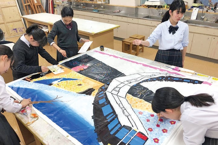 Japanese students make a painting as part of their joint activity with Pakistani students. — Dawn
