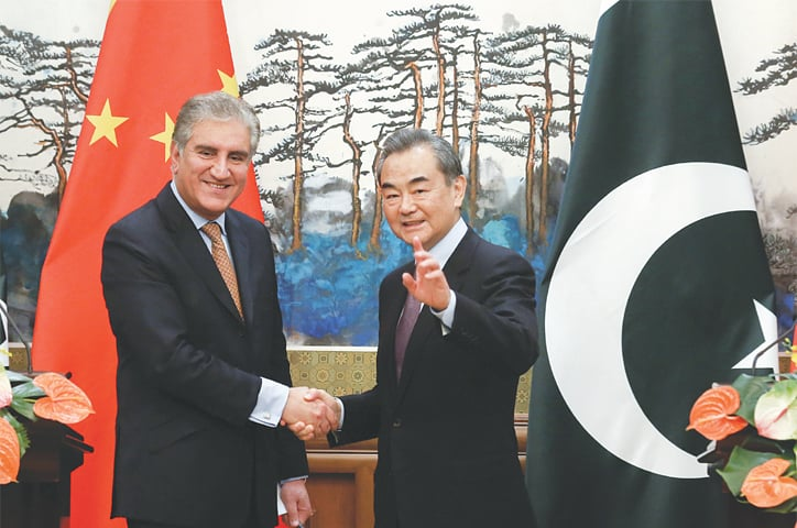 BEIJING: Foreign Minister Shah Mehmood Qureshi shakes hands with his Chinese counterpart Wang Yi after a news conference at the Diaoyutai State Guest House on Tuesday.—Reuters