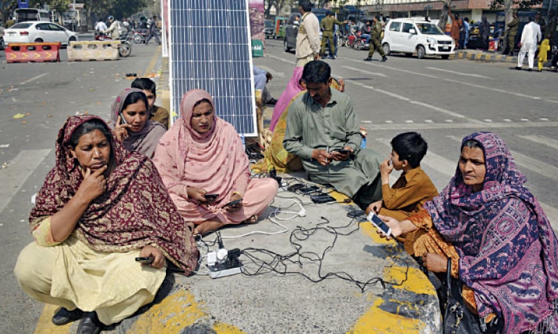 Lady health workers charge their mobile phones by using a solar panel during their sit-in at Charing Cross. — Online