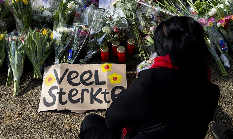 """A sign reads """"Lots of Strength"""" as a mourner lays flowers at a makeshift memorial for victims of a shooting incident in a tram in Utrecht, Netherlands on Tuesday, March 19, 2019. — AP"""
