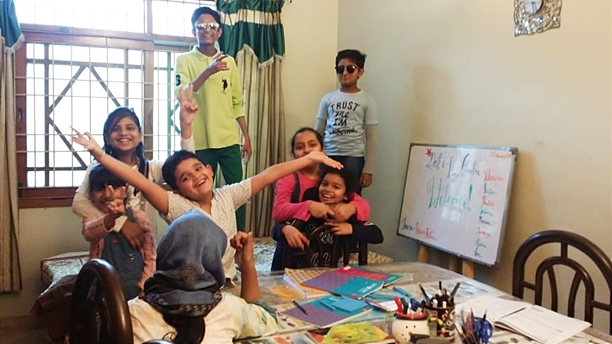 Happy students strike a pose during a maths session at Ambreen's house