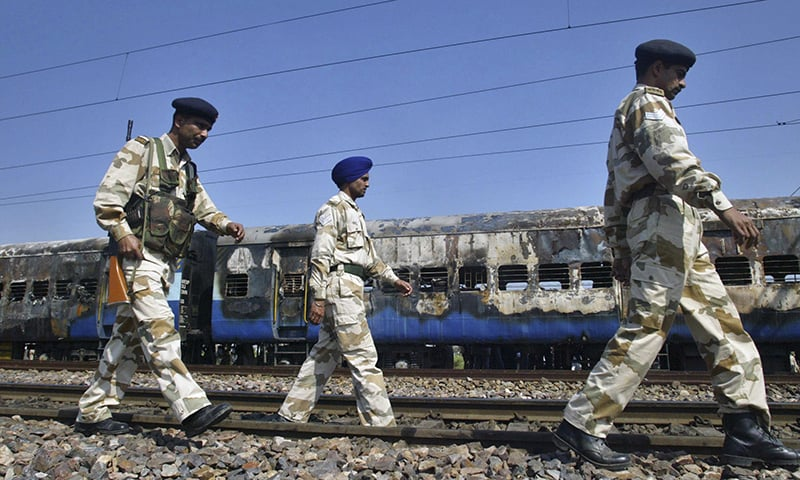 In this  Feb. 19, 2007 file photo, Indian security personnel walk past the charred coaches of the Samjhota Express train, which caught fire after a blast at Dewana, about 80 kilometres north of New Delhi, India. — AP