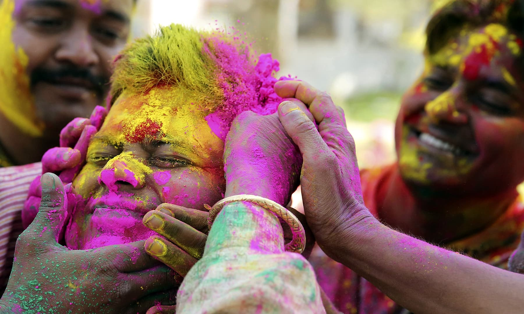 A man has coloured powder smeared on his face during celebrations marking Holi in Allahabad, India, March 20, 2019.  — AP