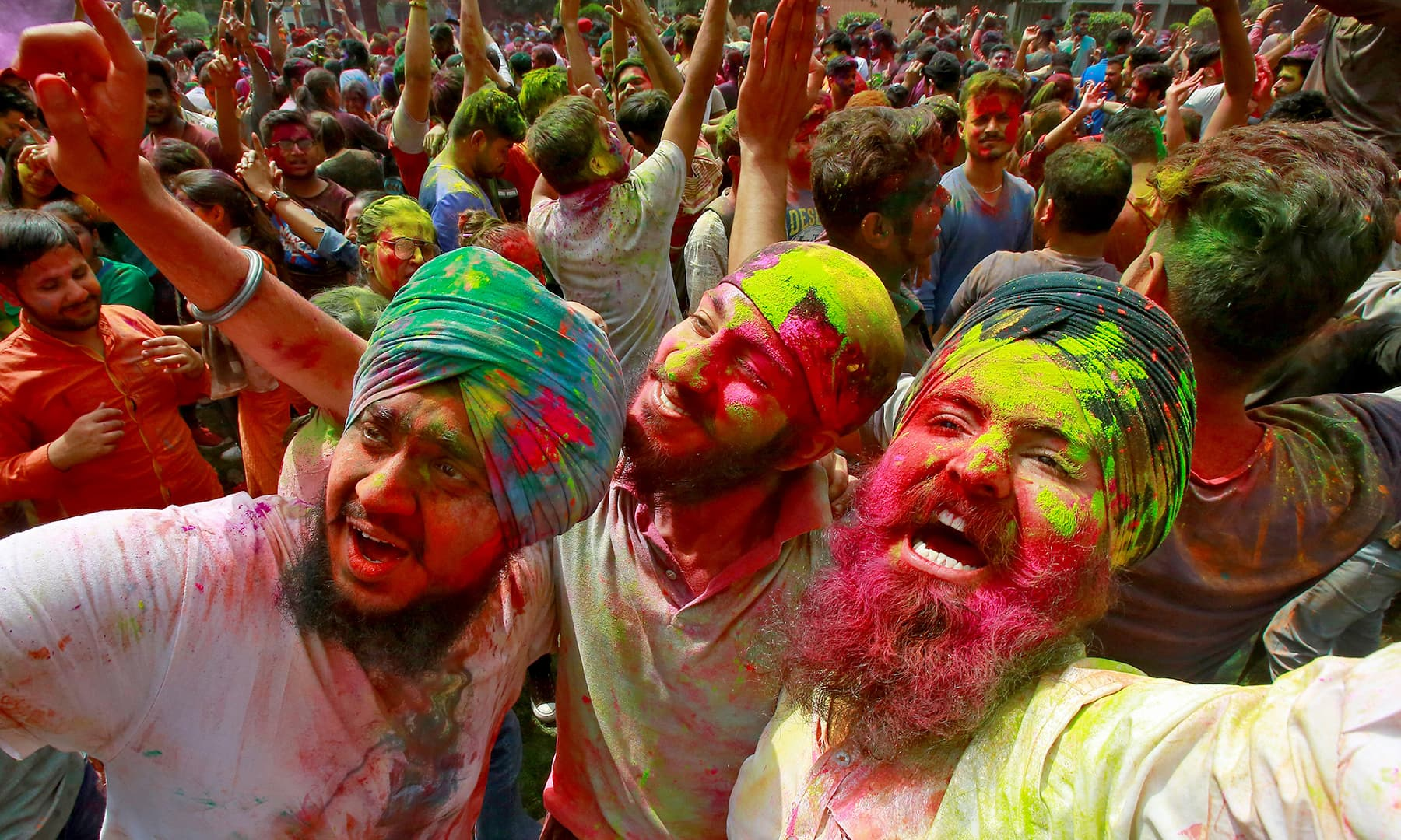 Students with their faces smeared in coloured powder dance as they celebrate Holi at a university campus in Chandigarh, India, March 20, 2019. — Reuters