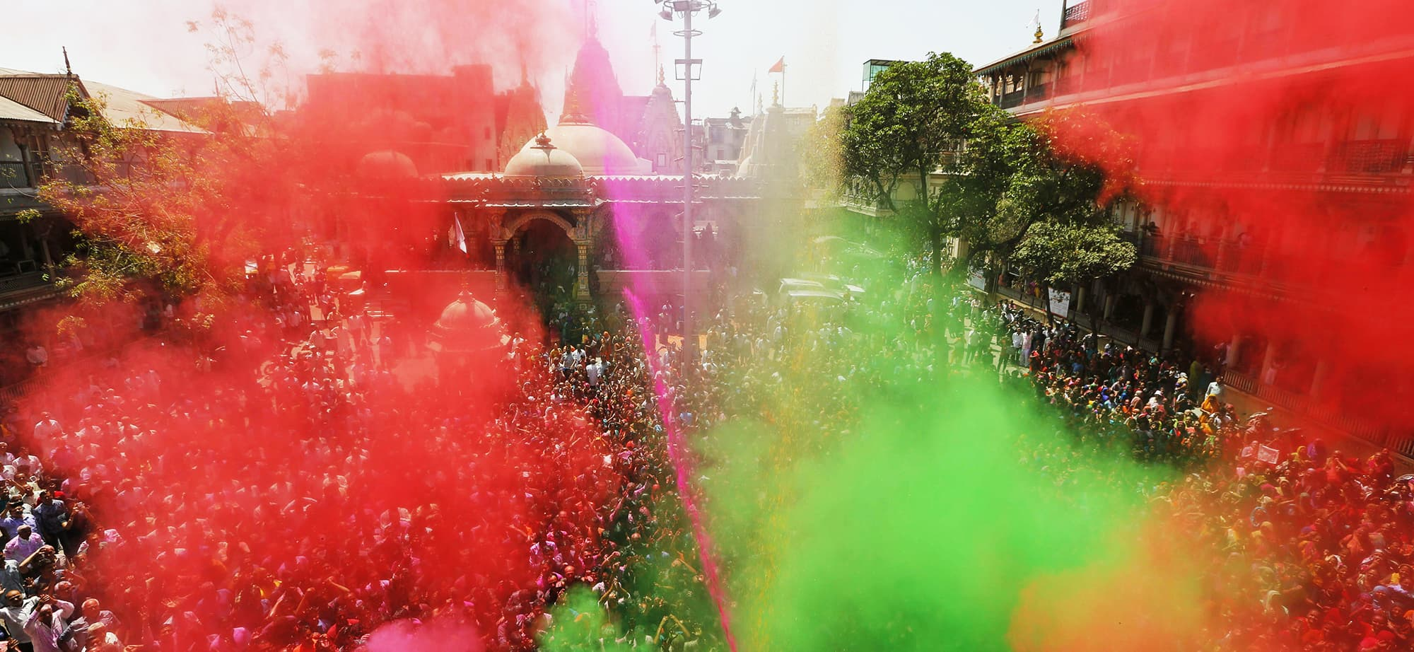 Indian Hindu devotees cheer as colored powder and water is sprayed on them by a Hindu priest during celebrations marking Holi at the Swaminarayan temple in Ahmadabad, India, Wednesday, March 20, 2019. Holi also marks the advent of Spring season. (AP Photo/Ajit Solanki) — Copyright 2019 The Associated Press. All rights reserved