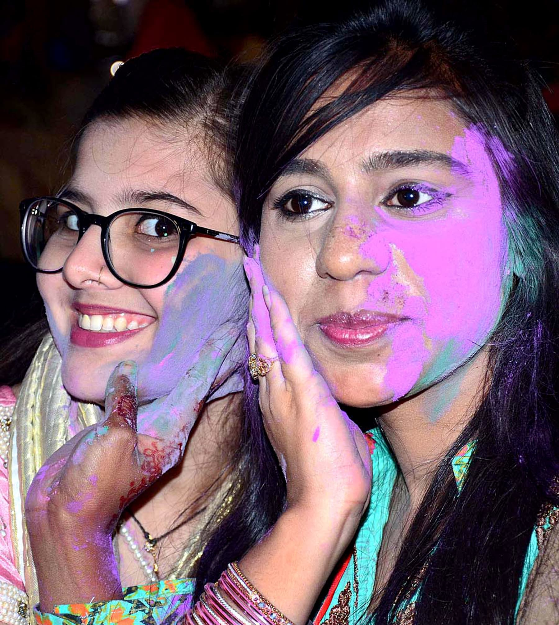 Girls pose for a photo after smearing each other's faces with paint in Hyderabad, Pakistan, on March 20, 2019. — APP