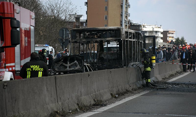 Firefighters stand by the gutted remains of a bus in San Donato Milanese, near Milan, Italy, March 21, 2019. — AP