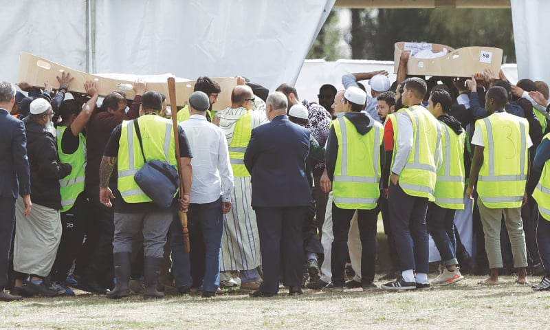 CHRISTCHURCH: Mourners carry the bodies of Khalid Mustafa and his son, Hamza, for burial at the Memorial Park Cemetery here on Wednesday.—AP