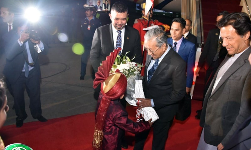Dr Mahathir receiving a bouquet of flowers as the prime minister looks on. — PID