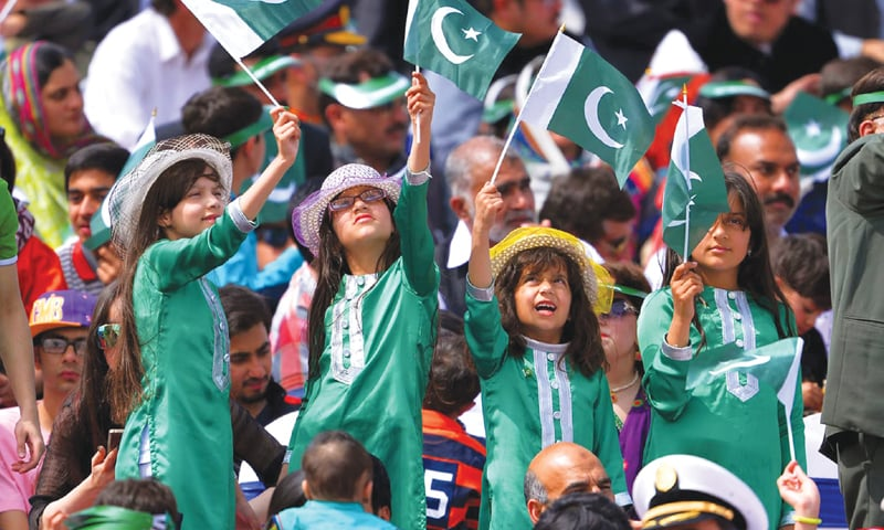 Young children waving the national flag at the Pakistan Day parade.