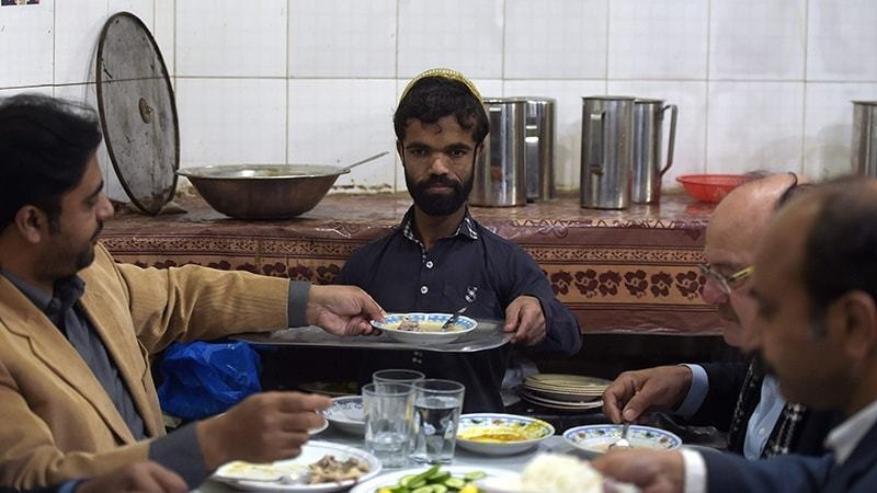 In this picture taken on Feb 22, 2019, Rozi Khan serves food to customers at Dilbar Hotel in Rawalpindi. — AFP