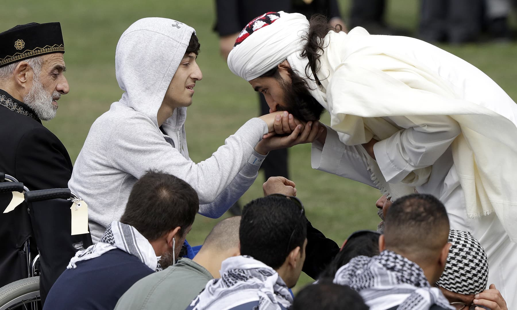 Zaid Mustafa, second left, son and brother of victims from last week's mosque shootings is welcomed to Friday prayers at Hagley Park in Christchurch. — AP
