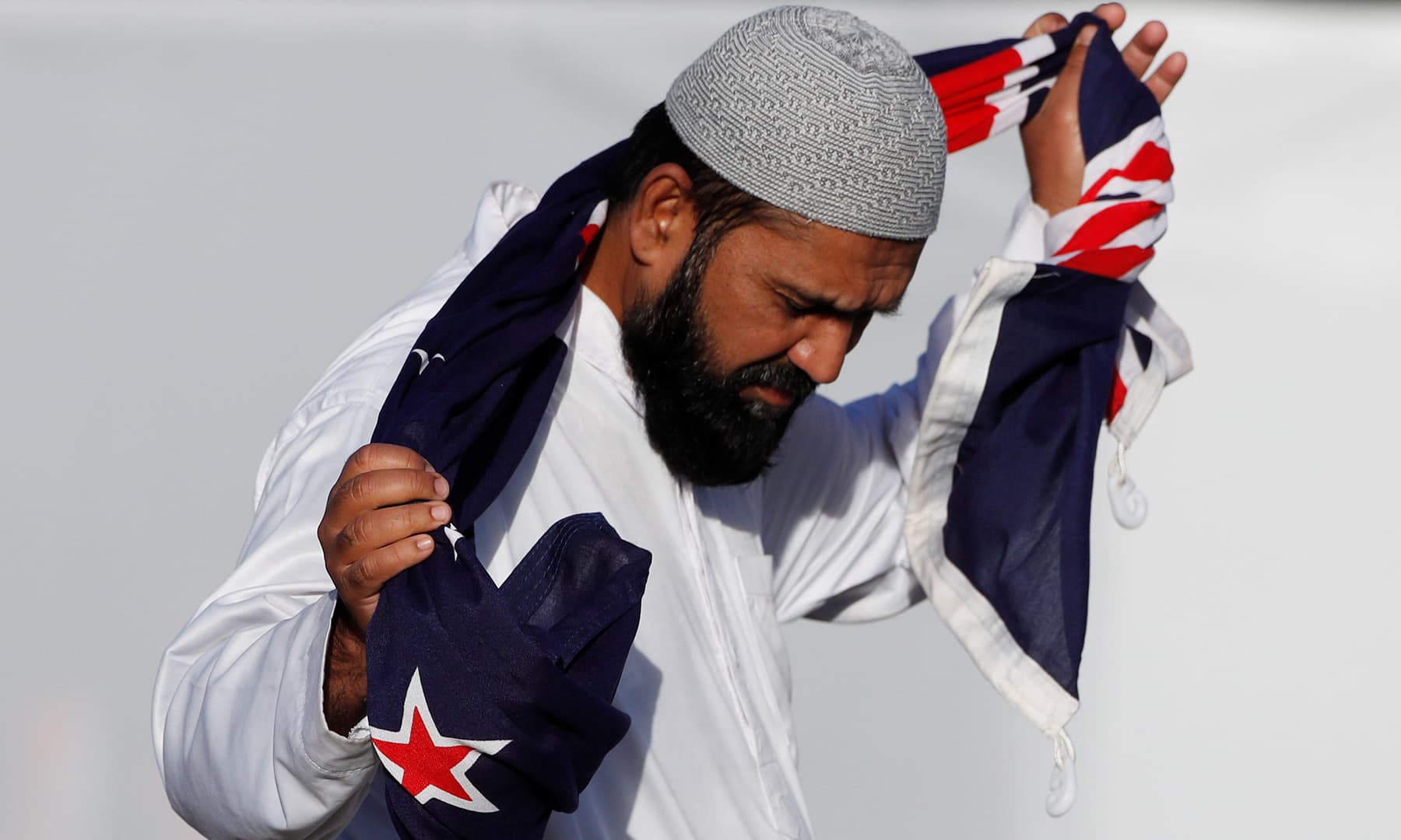 A man holding a New Zealand flag reacts during a burial ceremony for victims of the mosque attacks, at the Memorial Park Cemetery in Christchurch. — Reuters