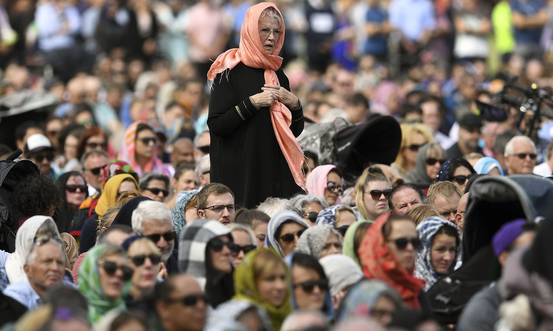 Members of the public look on during a gathering for congregational Friday prayers and two minutes of silence for victims of the twin mosque massacre, at Hagley Park in Christchurch. — AFP