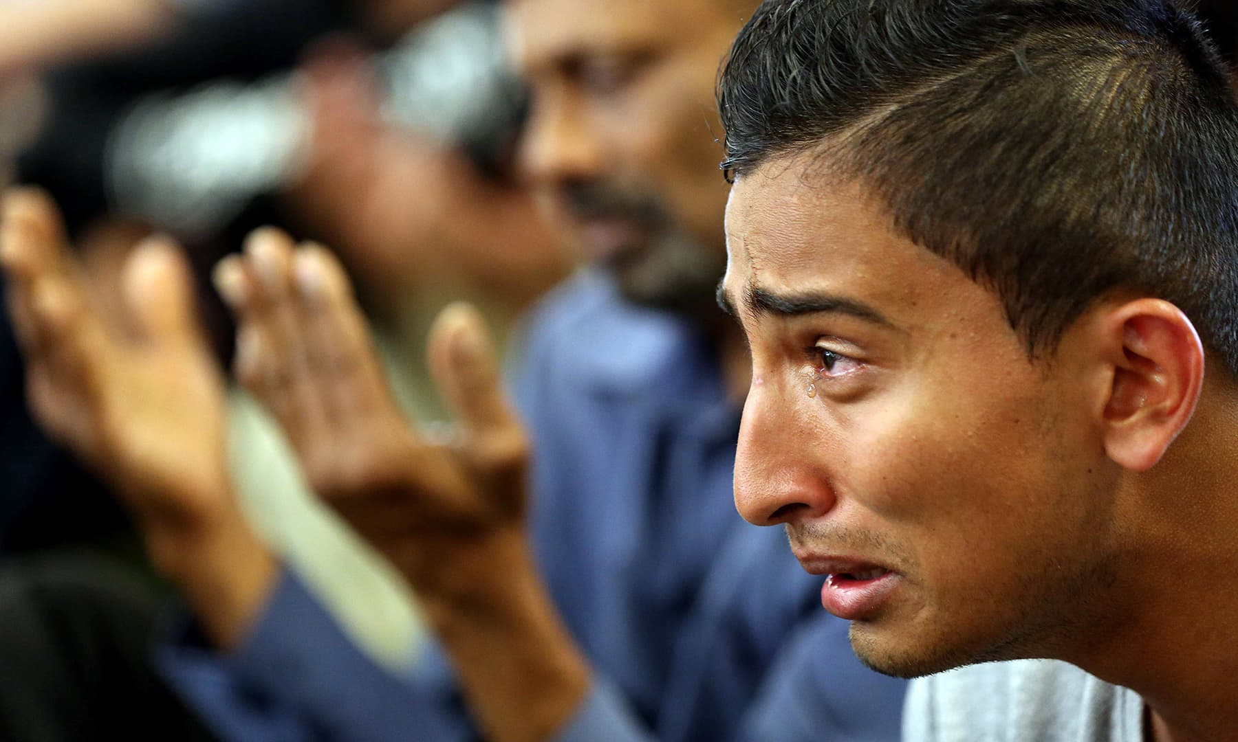 A youth cries during congregational Friday prayers at the Jamia Masjid mosque in Hamilton on March 22. — AFP