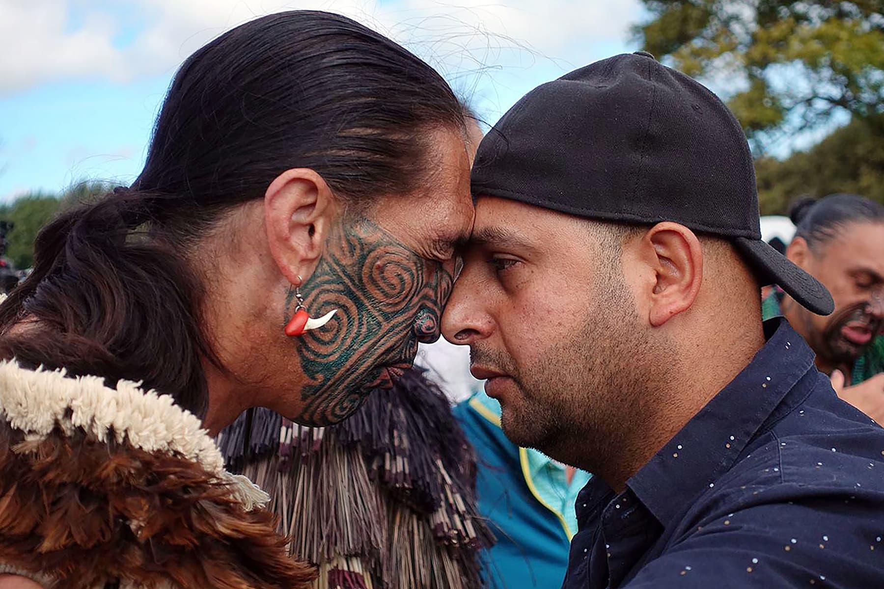 A Muslim man (R) and another local perform a traditional Maori 'hongi' greeting, a touching of noses, during a gathering for congregational Friday prayers at Hagley Park in Christchurch. — AFP