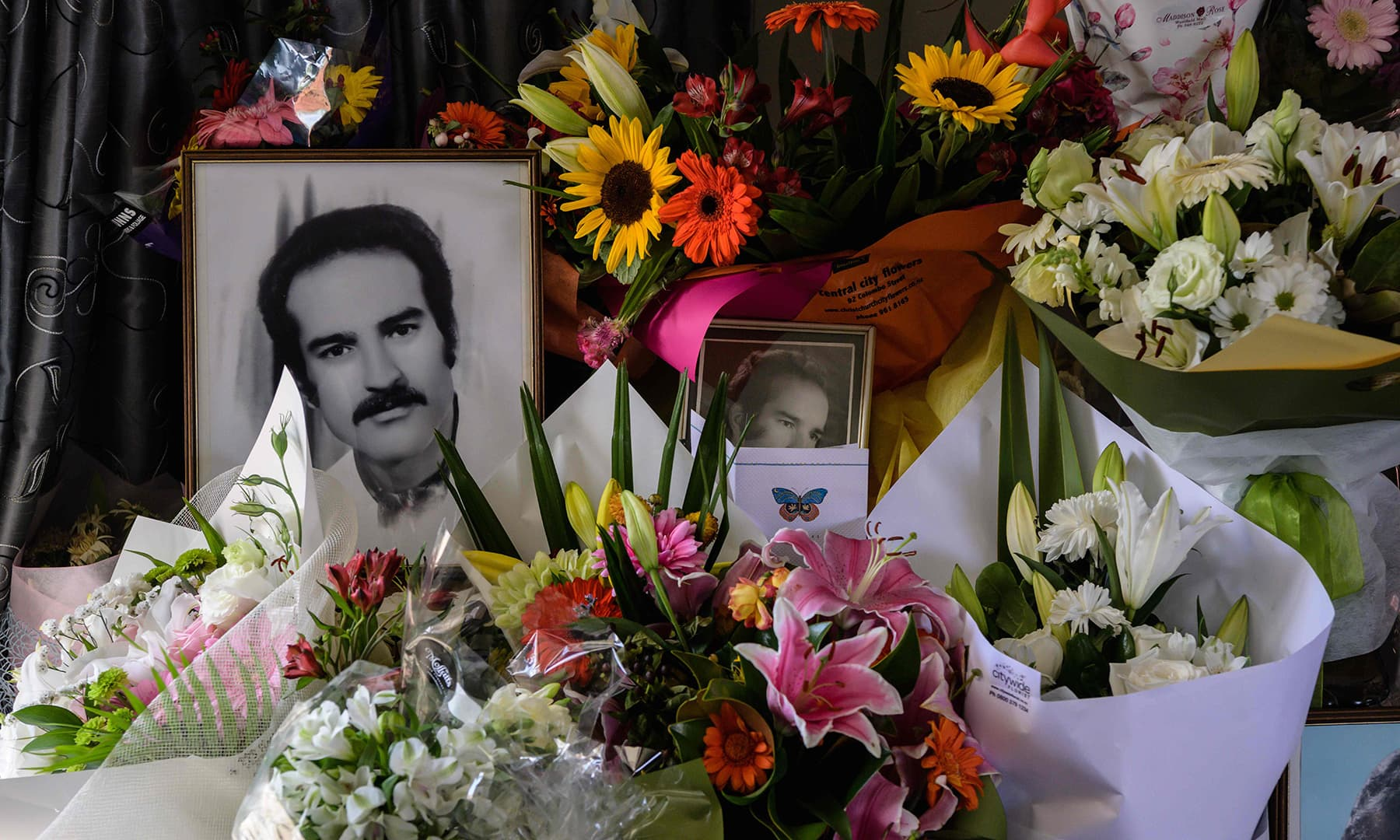 Flowers are placed around portraits at the home of Haji Mohammed Daoud Nabi, 71, in Chirstchurch. — AFP