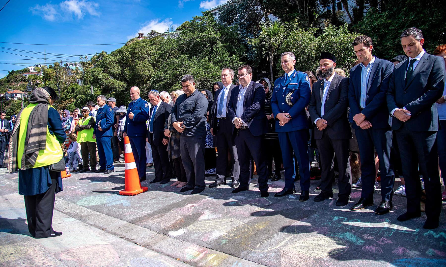 New Zealand officials observe two minutes of silence outside the Wellington Islamic Centre in Wellington on Friday. — AFP
