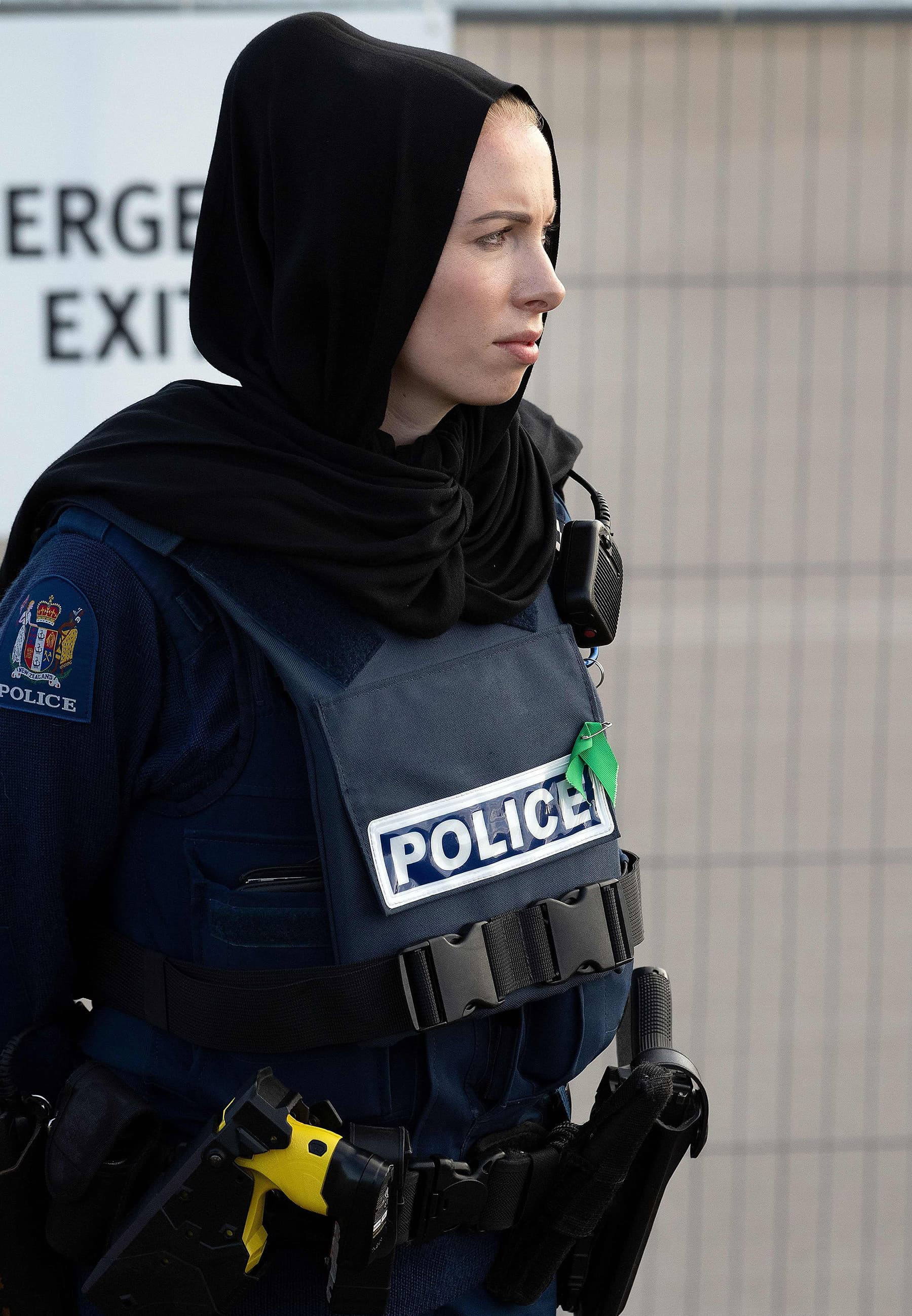 A police officer wearing a headscarf stands guard during a funeral ceremony at the Memorial Park in Christchurch on Friday. — AFP