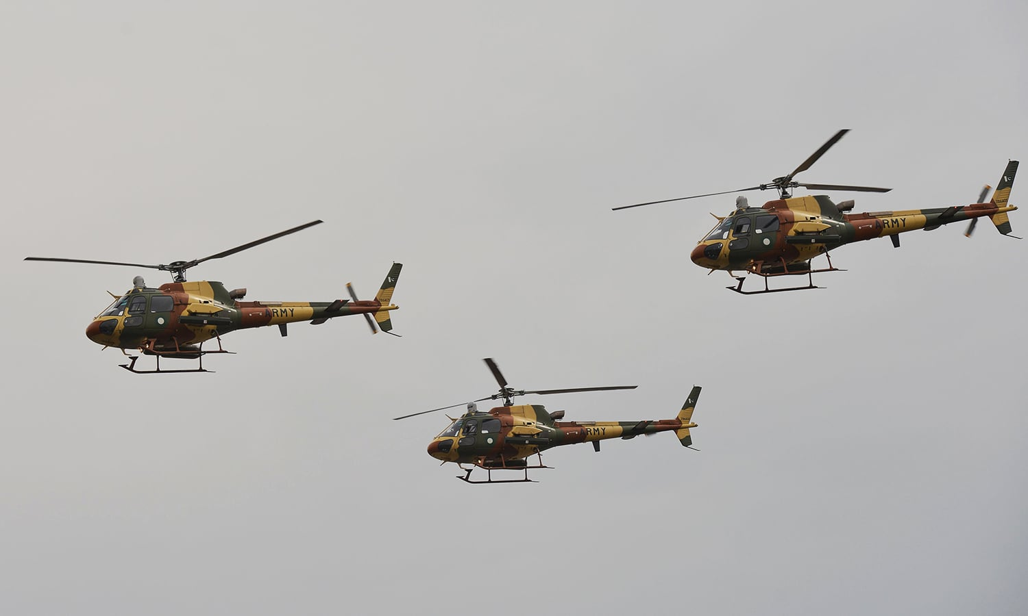 Army aviation helicopters fly past the Pakistan Day parade. ─ AFP