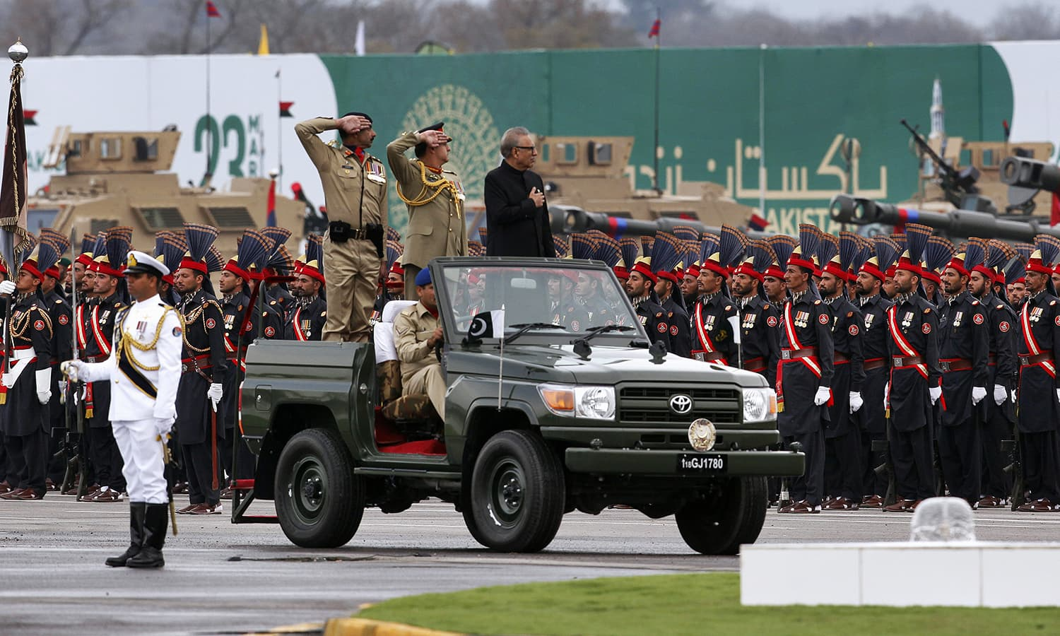 President Arif Alvi clad in a black sherwani stands atop a military vehicle to review the military parade. ─ AP