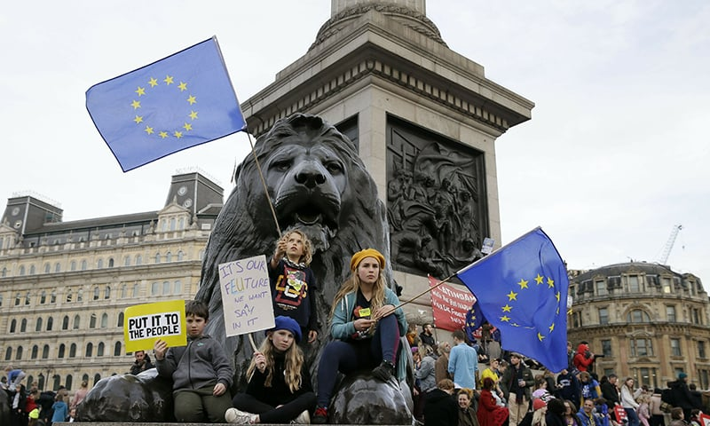 Demonstrators sit next to one of the lions in Trafalgar Square during a Peoples Vote anti-Brexit march in London. ─ AP