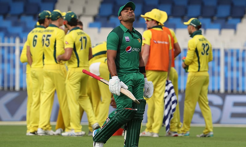 Pakistan's Umar Akmal leaves the field after being dismissed by Australia cricketer Nathan Lyon. — AFP