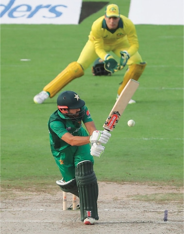 SHARJAH: Pakistan's century-maker Mohammad Rizwan plays through the onside as Australian wicket-keeper Alex Carey looks on during the second One day International at the Sharjah Cricket Stadium on Sunday.—AFP