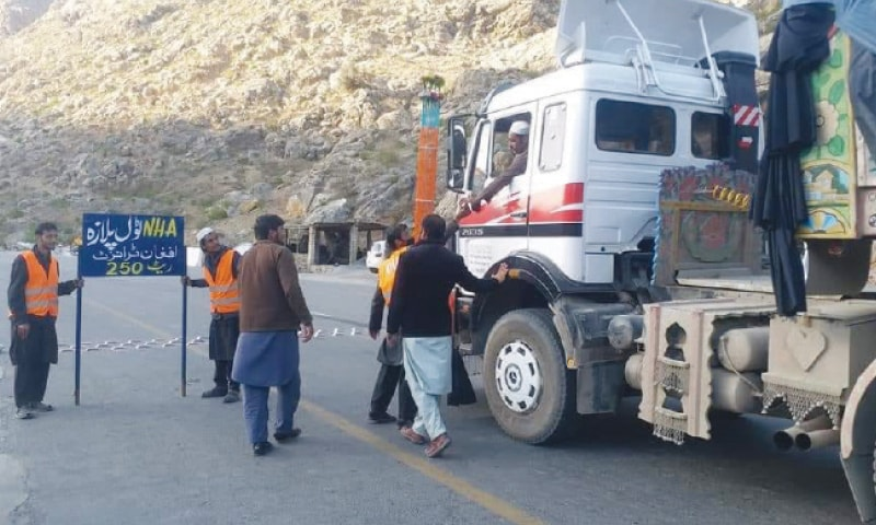 NHA staff collects toll tax from Afghan transit vehicles at Katta Khushtha, Khyber tribal district, where an NHA toll plaza was dismantled by transporters only a day before. — Dawn