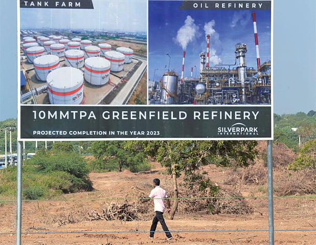 Hambantota: A man walks past a project plan board of the $3.85bn oil refinery project on Sunday.—Reufters