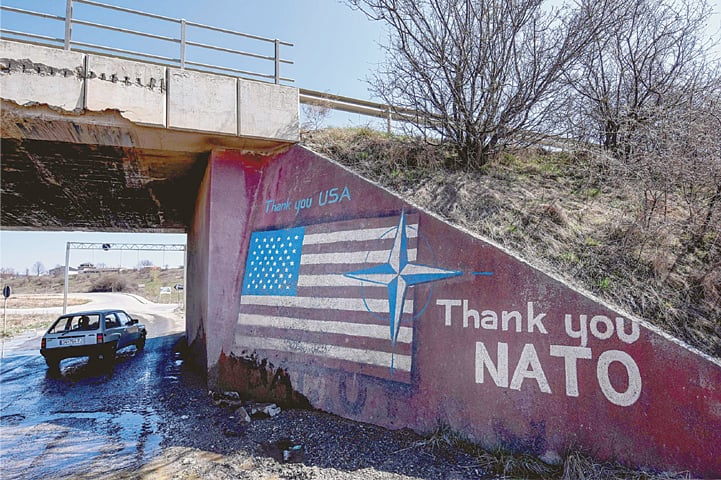 Stagovo (Kosovo): A car drives past a graffiti reading 'Thank You Nato' and featuring the US flag on Sunday.—AFP