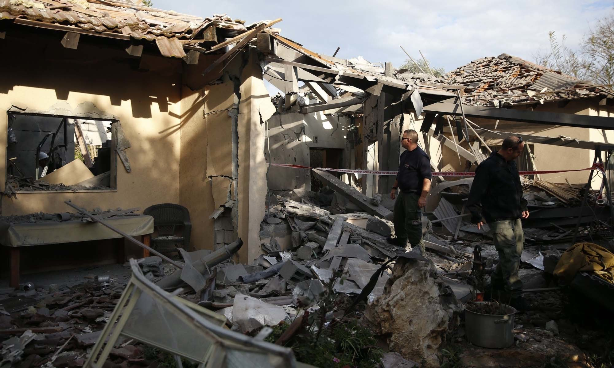 Police officers inspect the damage to a house hit by a rocket in Mishmeret, central Israel, on Monday, March 25, 2019. — AP