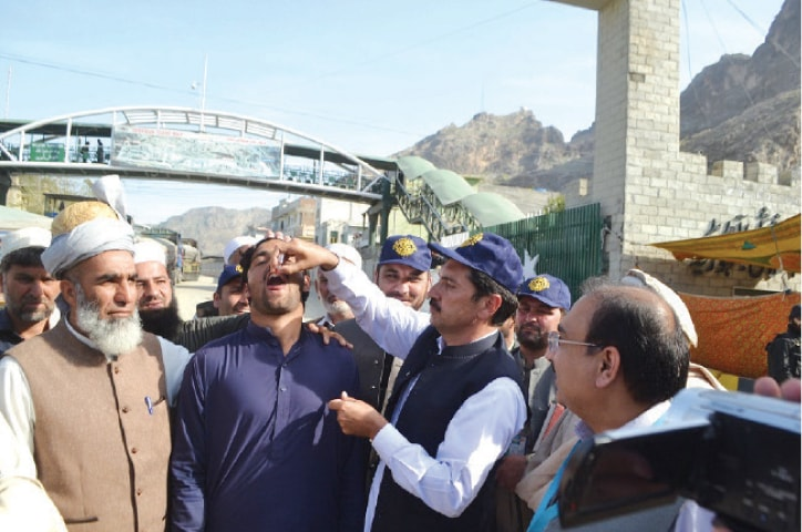An Afghan national is being given polio drops at Torkham border on Monday. — Dawn