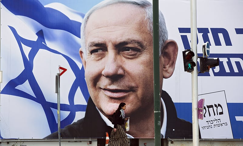 A woman walks by an election campaign billboard showing Israel's Prime Minister Benjamin Netanyahu, the Likud party leader, in Tel Aviv, Israel, on Thursday. — AP