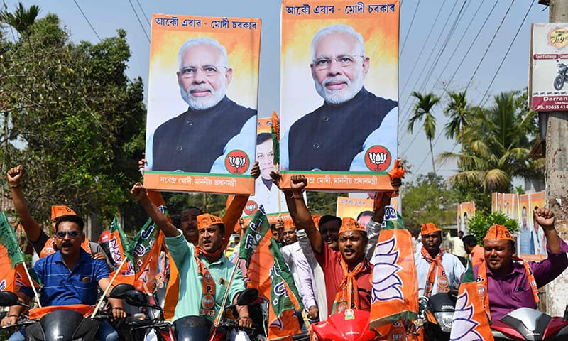 Supporters of the Bharatiya Janata Party (BJP) carry posters of India's Prime Minister Narendra Modi as they take part a motorcycle rally as part of the election campaign in Mangaldai, some 74km from Guwahati, the capital city of India's northeastern state of Assam on March 29. — AFP