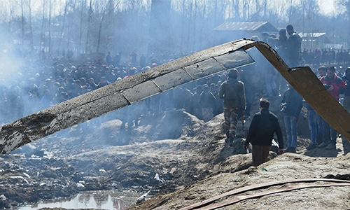 Indian soldiers and onlookers stand near the remains of an Indian Air Force helicopter after it crashed in occupied Kashmir's Budgam district, outside Srinagar on February 27, 2019. — AFP/File