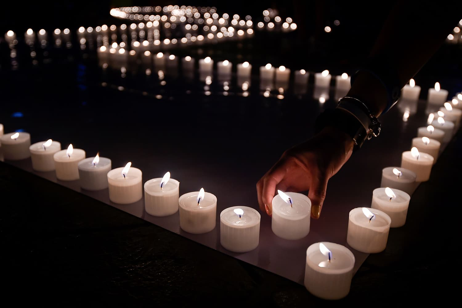 People light candles and form the 60+ sign on March 30, 2019 in Cali, Colombia. ─ AFP