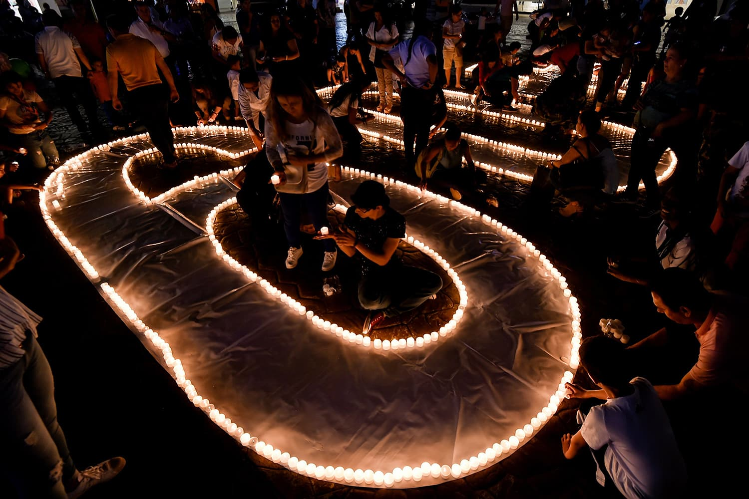 People light candles and form the 60+ sign on March 30, 2019 in Cali, Colombia, during Earth Hour. ─ AFP
