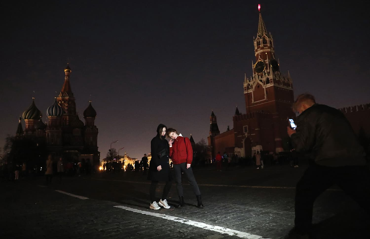 "A man takes photo of two women posing at the Red Square during the ""Earth Hour"" campaign in central Moscow. ─ AFP"