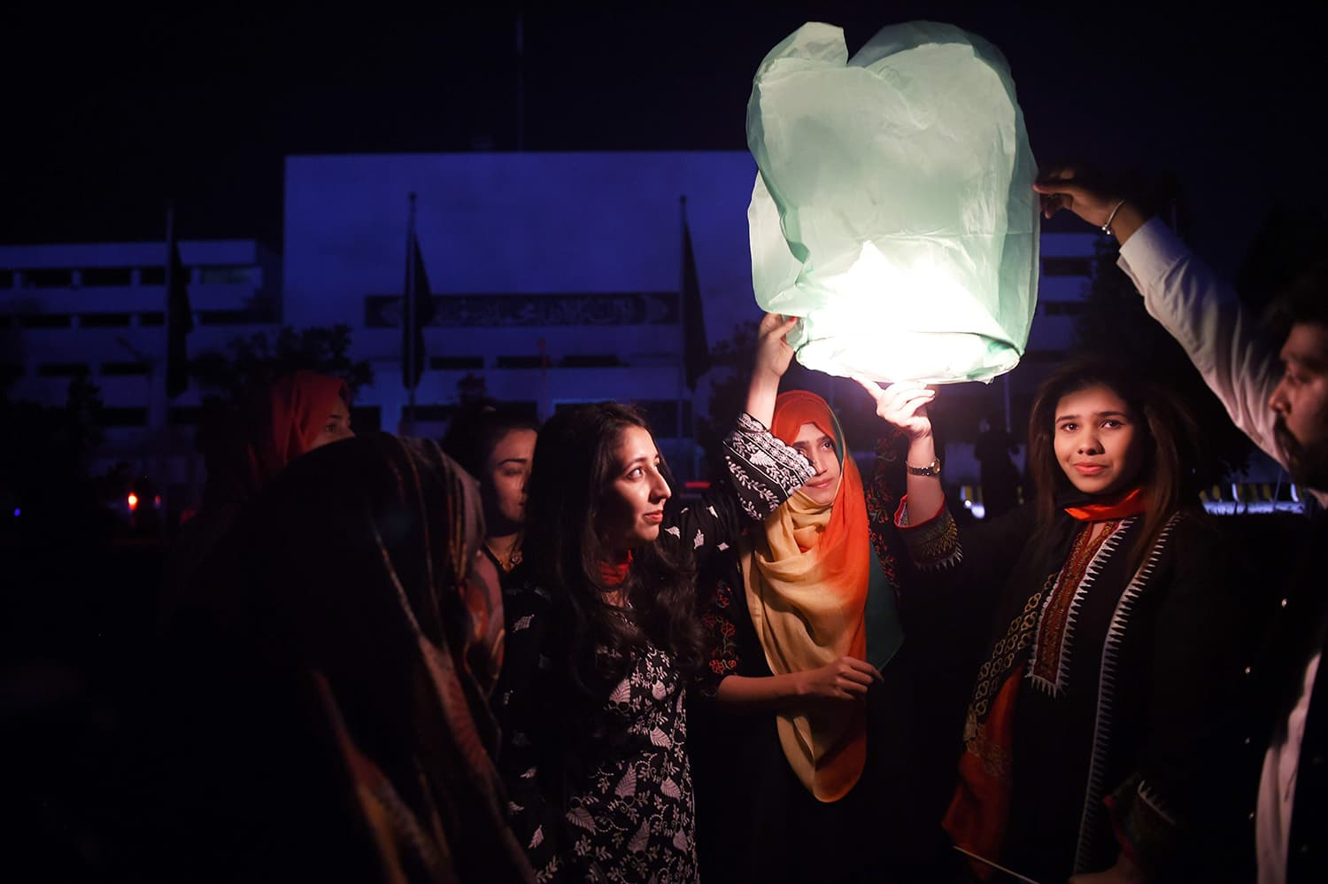 Girls release floating lanterns in front of Parliament House during Earth Hour in Islamabad. ─ AFP
