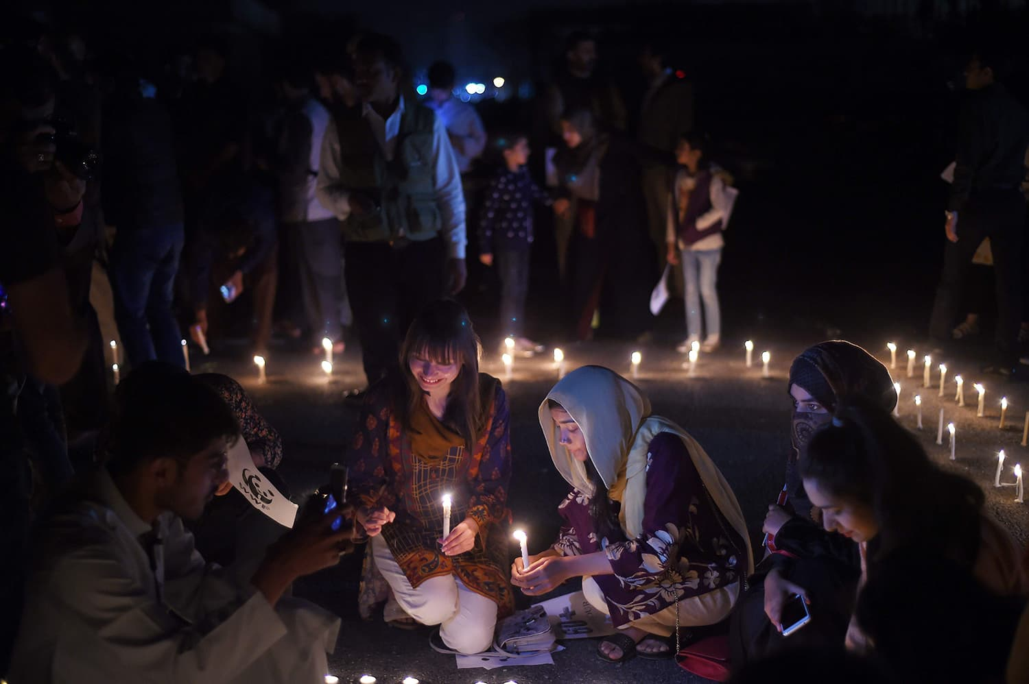 Girls hold candles in front of Parliament House during Earth Hour in Islamabad. ─ AFP