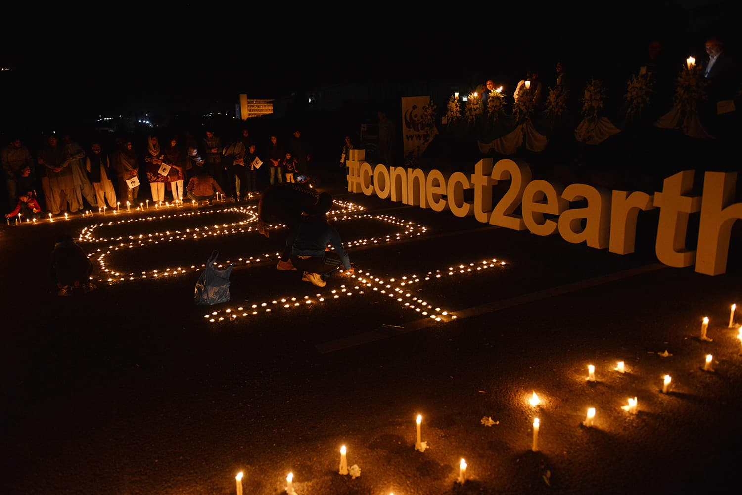 People light candles in front of Parliament House during Earth Hour in Islamabad . ─ AFP
