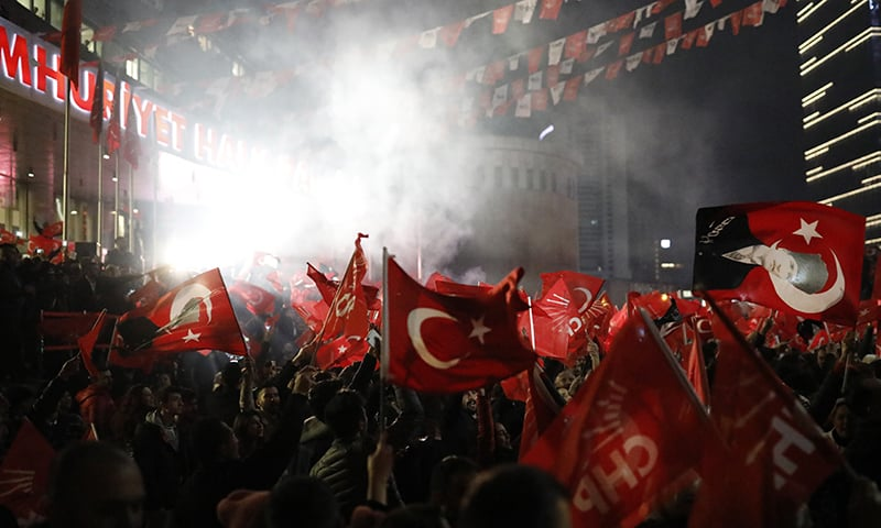 Supporters of the Republican People's Party, CHP, wave Turkish flags, and one with a portrait of Kemal Ataturk, right, as they celebrate after preliminary results of the local elections were announced in Ankara, Turkey. ─ AP