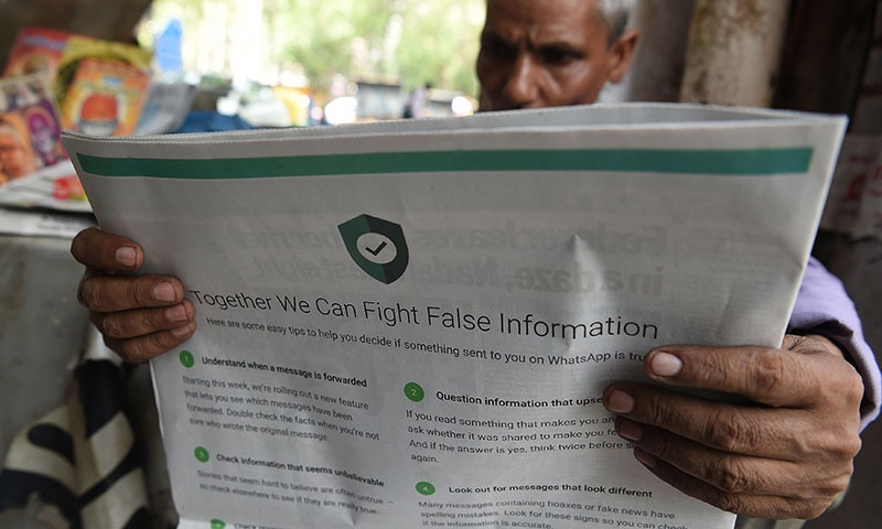 This file photo illustration taken on July 10, 2018 shows an Indian newspaper vendor reading a newspaper with a full back page advertisement from WhatsApp intended to counter fake information, in New Delhi. — AFP