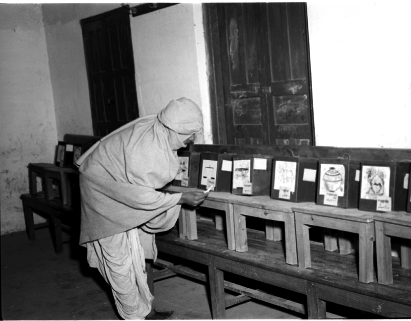 A villager looking for the sign (election symbol) of a candidate of his choice at a polling station in Delhi on January 14, 1952.—Wikimedia Commons