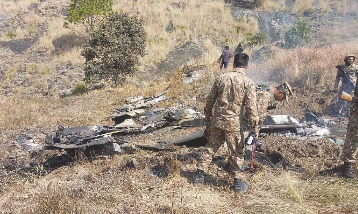 Pakistani soldiers stand near the remains of an Indian fighter jet shot down by Pakistan near the Line of Control on February 27, 2019 | AFP