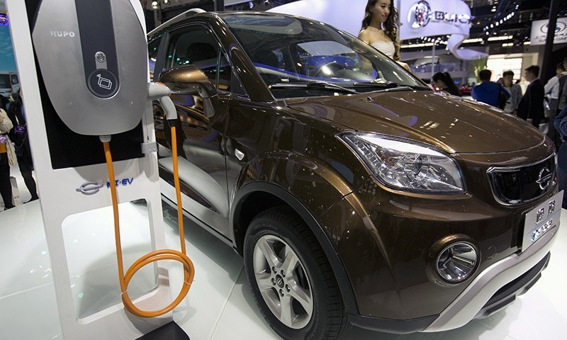 The file photo shows a staff member stands next to an e.Cool electric SUV by Chinese automaker Changjiang on display at the Beijing International Automotive Exhibition in Beijing.—AP/File
